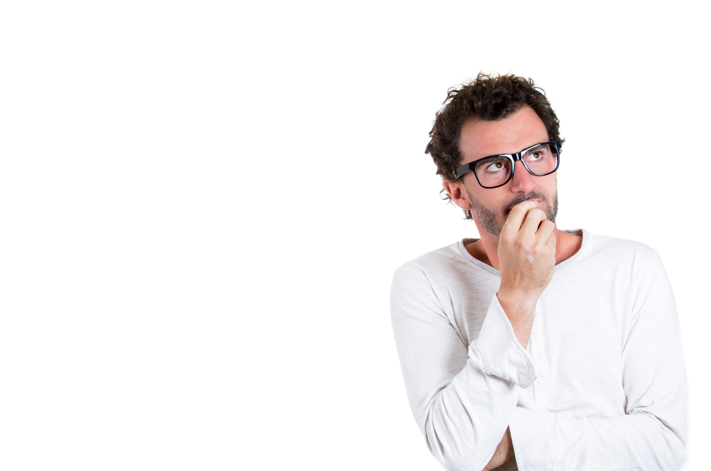 Closeup portrait of handsome young man, wearing black glasses, daydreaming, deep in thought  looking up and to side, isolated on white background with copy space. Human emotions and facial expressions