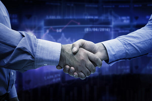 Men shaking hands against stocks and shares