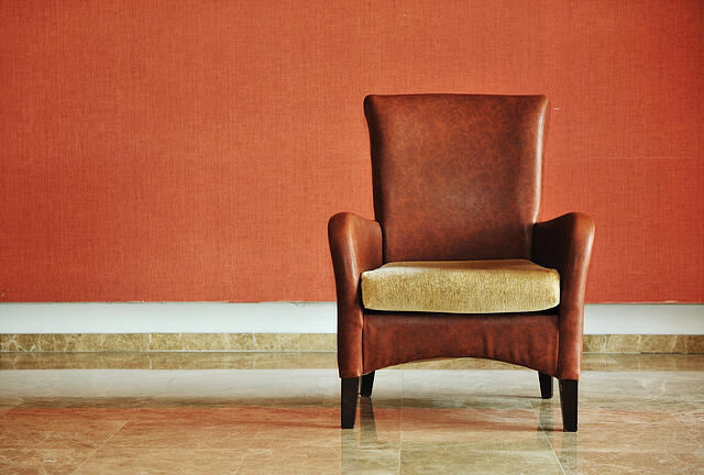 vintage brown-gray chair standing beside the wall